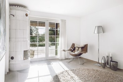 Den store svenske kamin både varmer og hygger enormt. Den er smuk at se på, og så er den faktisk den eneste ting, der fik lov til at blive i huset fra de tidligere ejere.