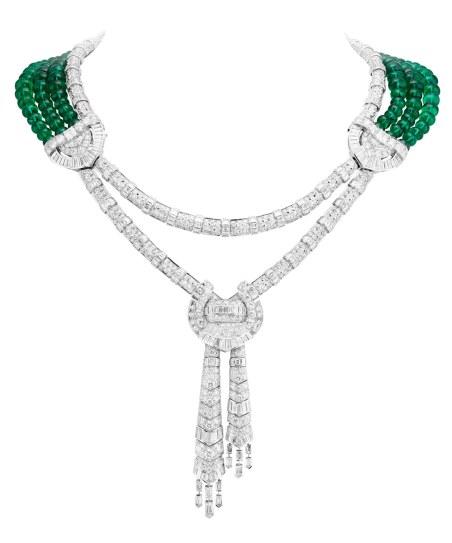 Van Cleef & Arpels' 'Drapé Majestueux'-unikahalskæde af 18 karat hvidguld med runde, firkantede, asscher-, baguetteog obus-slebne diamanter og 150 zambianske smaragdkugler (i alt 244.24 carat – hver kugle på mellem 6-8 mm i diameter). Halskæden er genialt konstrueret til at være 'vendbar', så smaragderne enten kan bæres i nakken med diamanterne i front eller omvendt.