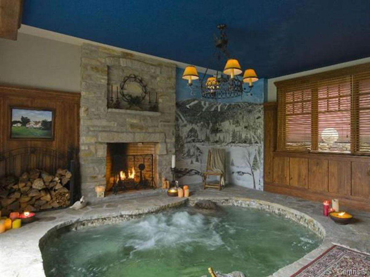A Quebec Chalet With A Fireplace Next To The Hot Tub