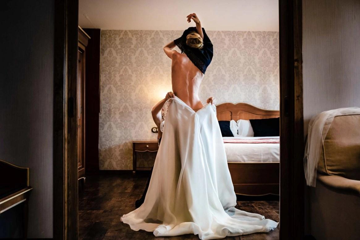 Foto boda sensual novia subiéndose el vestido de espaldas en una habitación lujosa y estilo clásico
