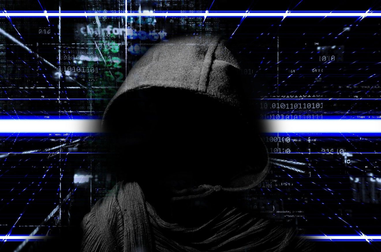 A depiction of cybercriminal in a black hoodie with a tech-related backdrop.