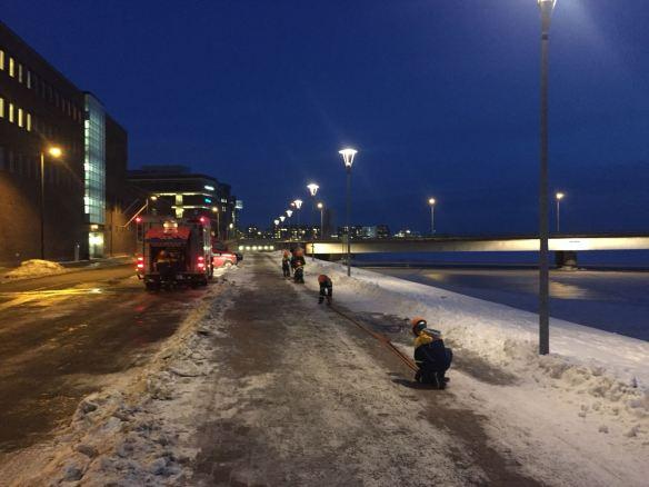 Palokuntanuoret rullaavat letkuja kasaan Lauttasaaren sillan kupeessa