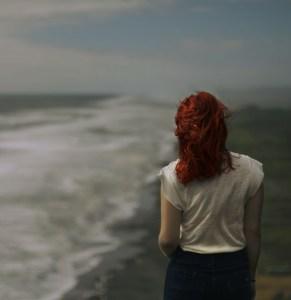 Redhead woman walking by ocean meditating on Greatest Overcomer