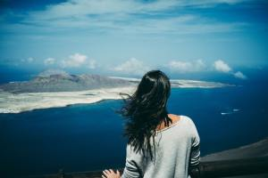 young woman watching ocean view and island in horizon, thinking