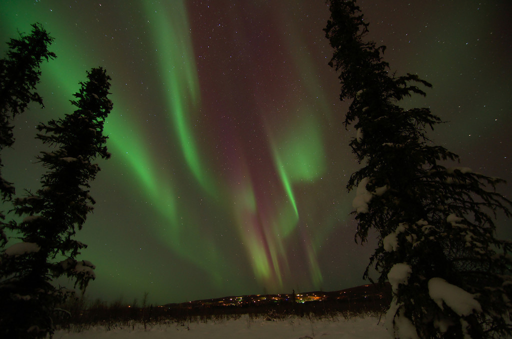 Aurora borealis bands over town lights in Fairbanks, Alaska