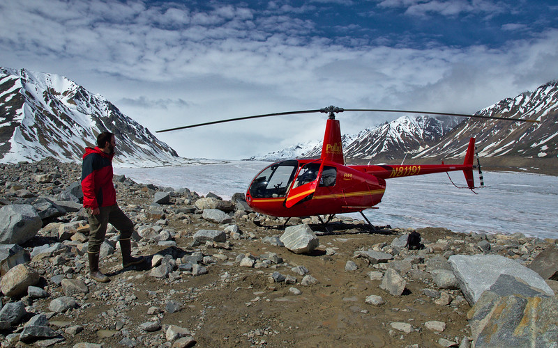 Our R44 pilot, Brandon, next to the helicopter before leaving the moraine on Black Rapids for the last time.