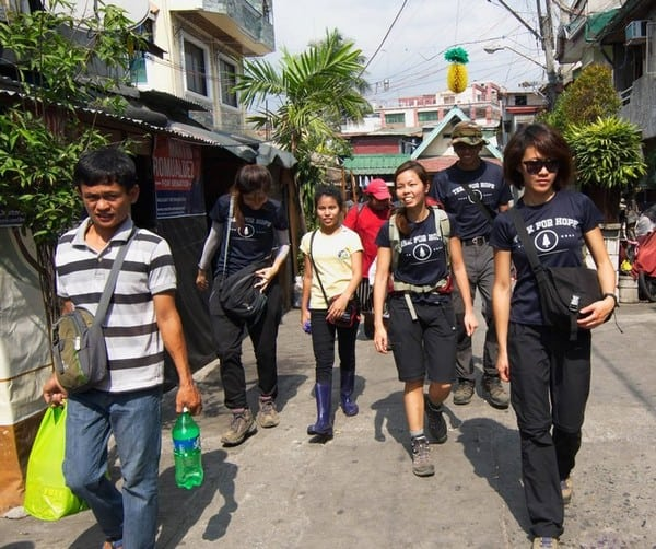 Walking through the housing area of these people in manila bring food rations to the residents