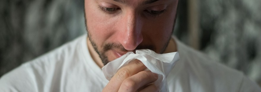 man with cold flu symptoms wiping nose with tissue