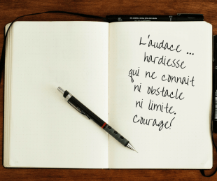 Livre ouvert avec un crayon dessus où il est inscrit : L'audace... hardiesse qui ne connait ni obstacle ni limite. Courage!