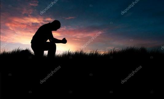 homme en prière avec un coucher de soleil