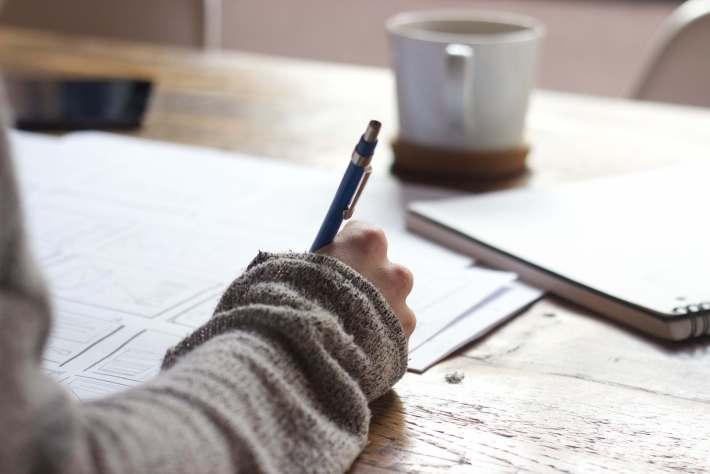 personne dont nous voyons seulement la main et qui écrit sur des feuilles de papier