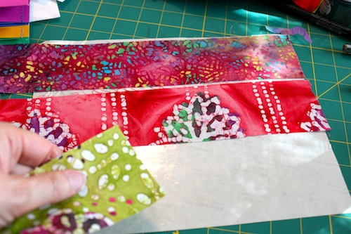 Placing fabric strips onto adhesive sheet