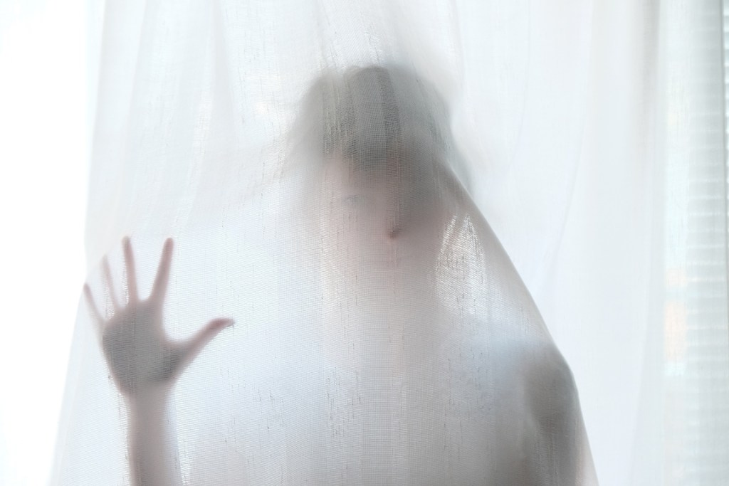 a girl behind a sheer curtain trying to see through the haze