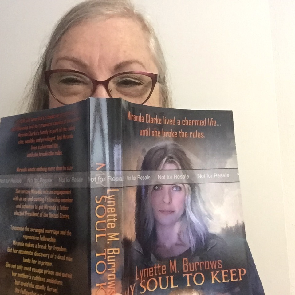 Photo of me peering over the top of my book, My Soul to Keep. I had a big dream and I made it happen.