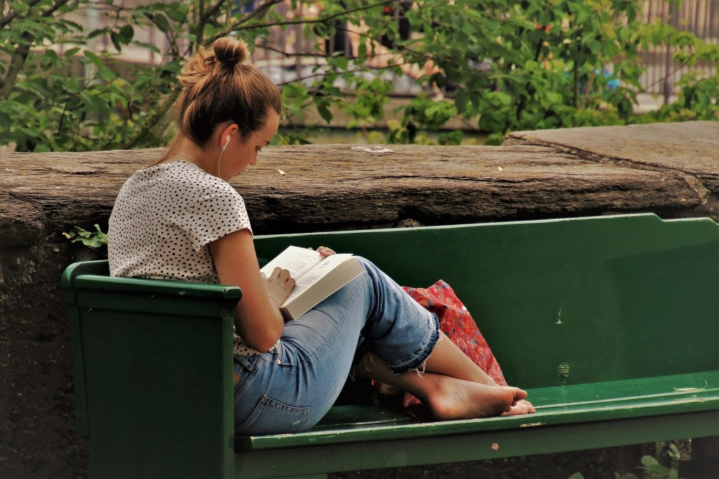Photo of a girl sitting on a bench and reading a book--What your book review can do is powerful.