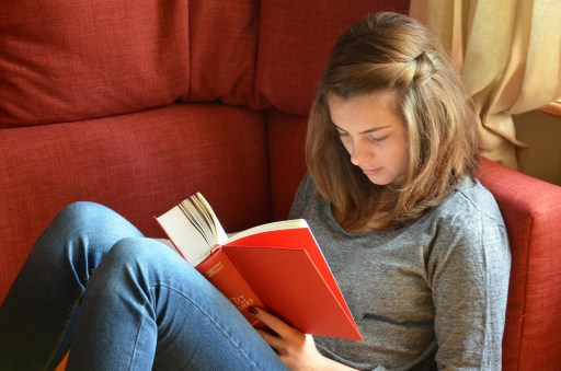 Image of woman on red sofa, reading a book.