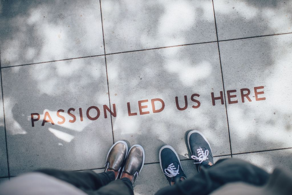 "Looking down at two pair of feet on a patio with the words ""passion led us here."" One of five tips for staying motivated."