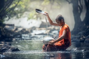 Image of a boy performing the Buddhist water ritual. Develop a personal ritual to care for yourself during difficult times.