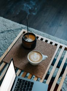 Image of coffee and burning incense next to a laptop computer. Develop a personal ritual to care for yourself during difficult times.