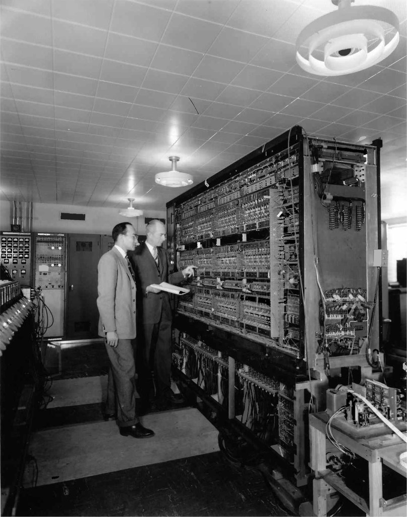 Two men stand and flip switches on a massive machine with rows of switches, the first Argonne Computer looks something like the Multivac in The Last Question reviewed by LynetteMBurrows.com