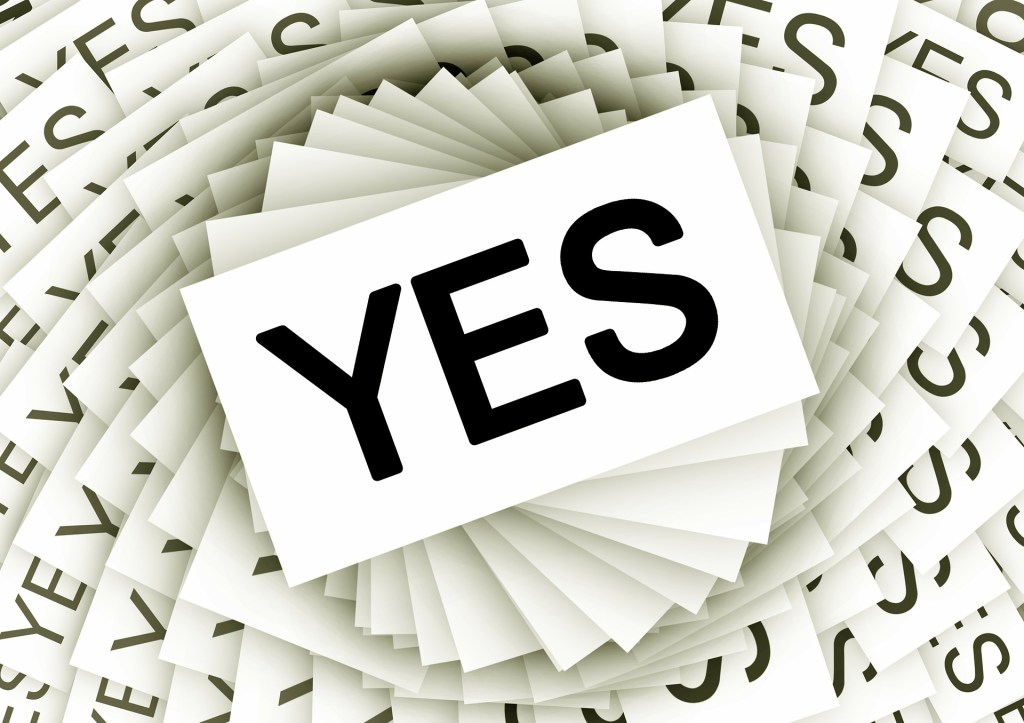 A stack of cards with the word yes on them--say yes too often? that's why you need to fail people pleasing