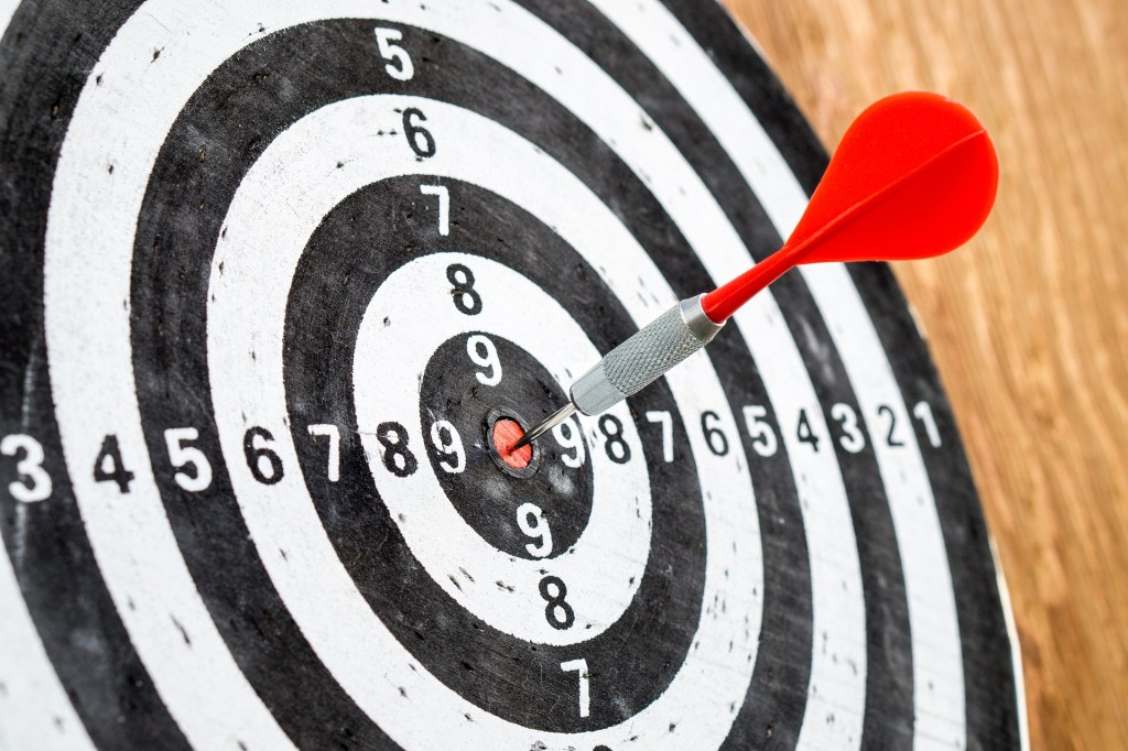 Image of a dart stuck in the red bullseye of a target is a symbol of the goals I hit and the opportunities for the new quarter.