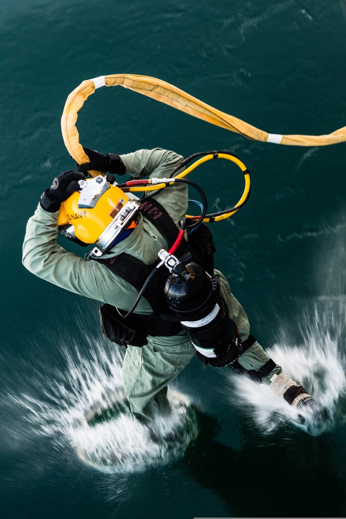 Image of U.S. Navy Diver wearing helmet and oxygen tank entering the water
