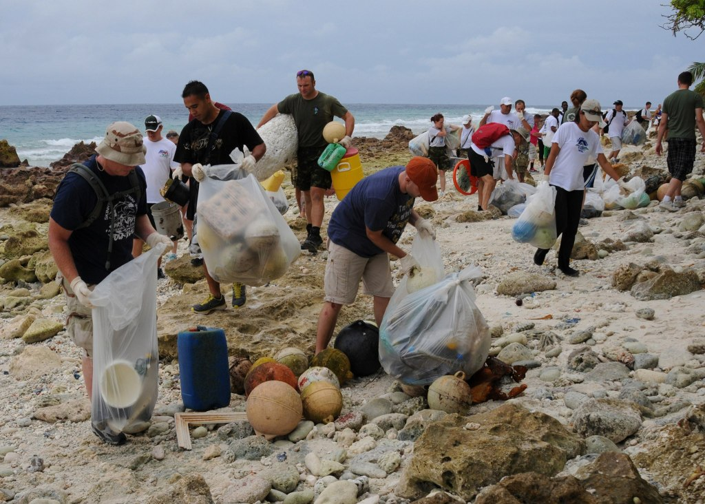 Look for the good news--service members and residents picking up bags of trash on beach of Diego Garcia.
