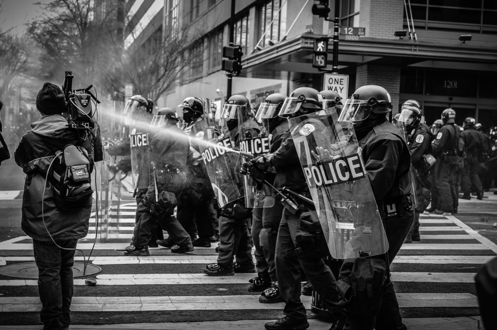 Image of protestors being sprayed by police--the reality of freedom for some isn't really free