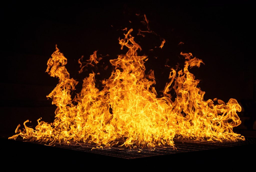 Image of flames leaping high into the night--a symbol of too many are hurting