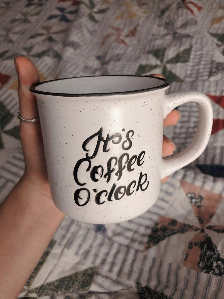 "Mug inscribed with  ""It's coffee o'clock"" held the elixir of the desperately sleep deprived me"