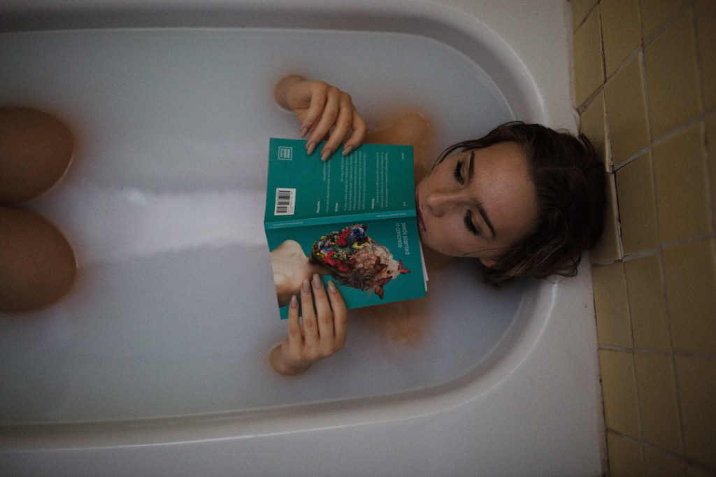 A woman taking a bubble bath while reading