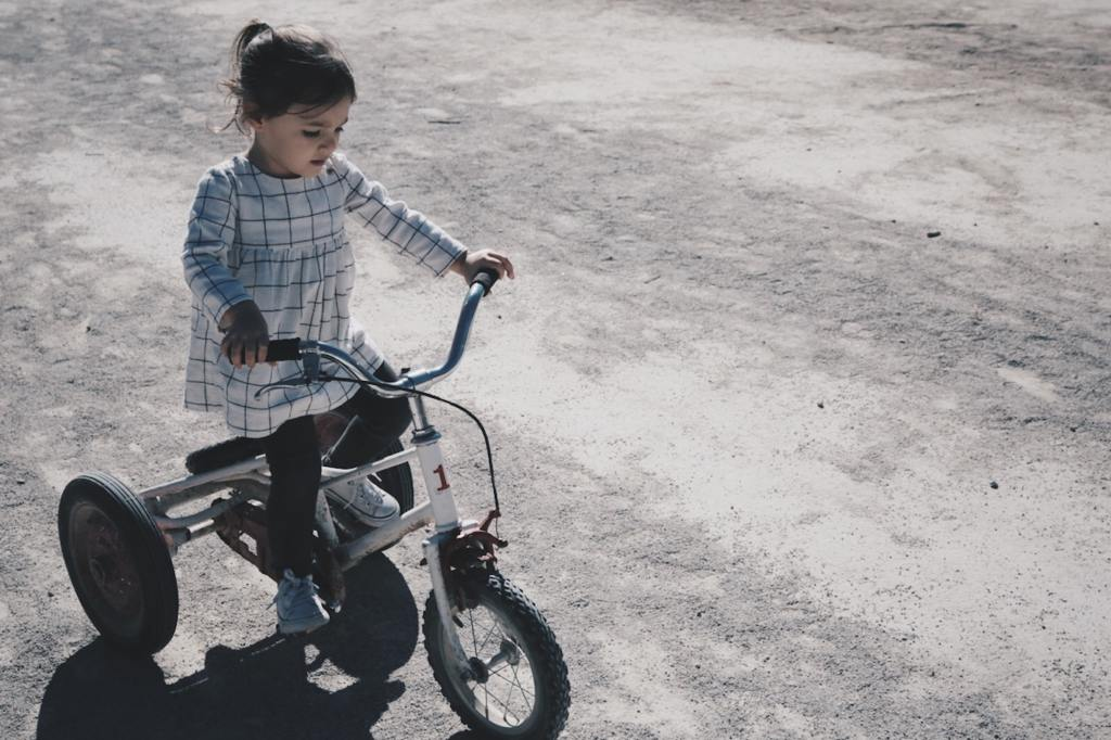 young girl riding a tricycle
