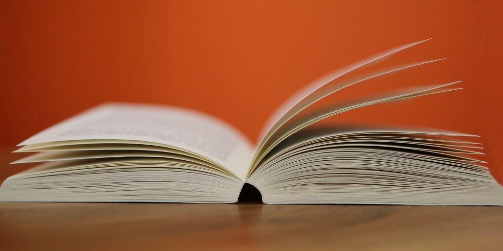a book open to the middle where you can learn that a strong midpoint powers your novel