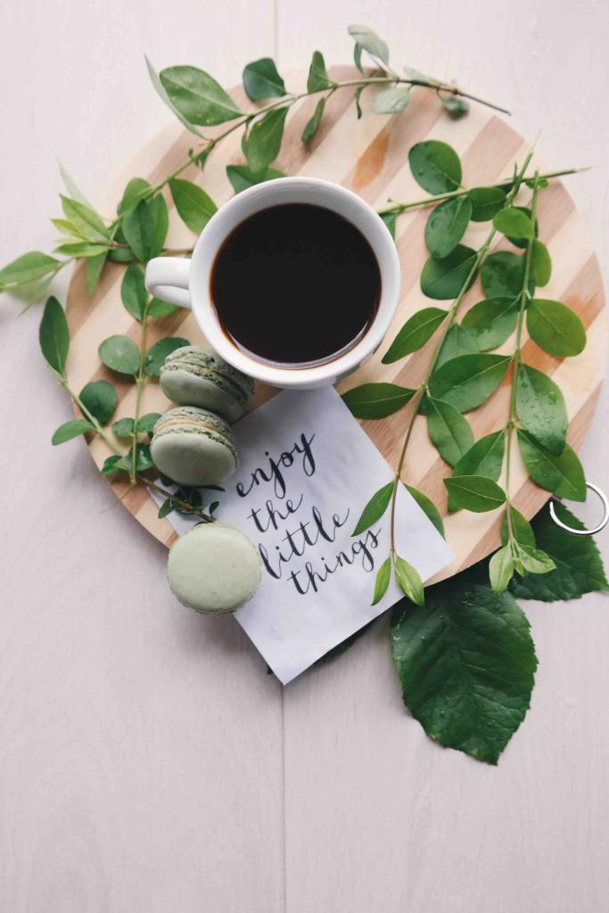 A photo looking down on a cup of coffee, some sprigs of mint, and some cookies on a round wooden cutting board with a handwritten note that urges you to enjoy the little things-perhaps the perfect time to visit your gratitude
