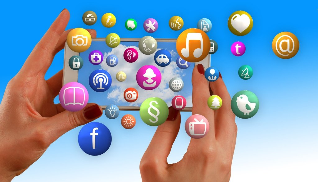 hands holding a smartphone with icons of social networks floating above and around the phone.