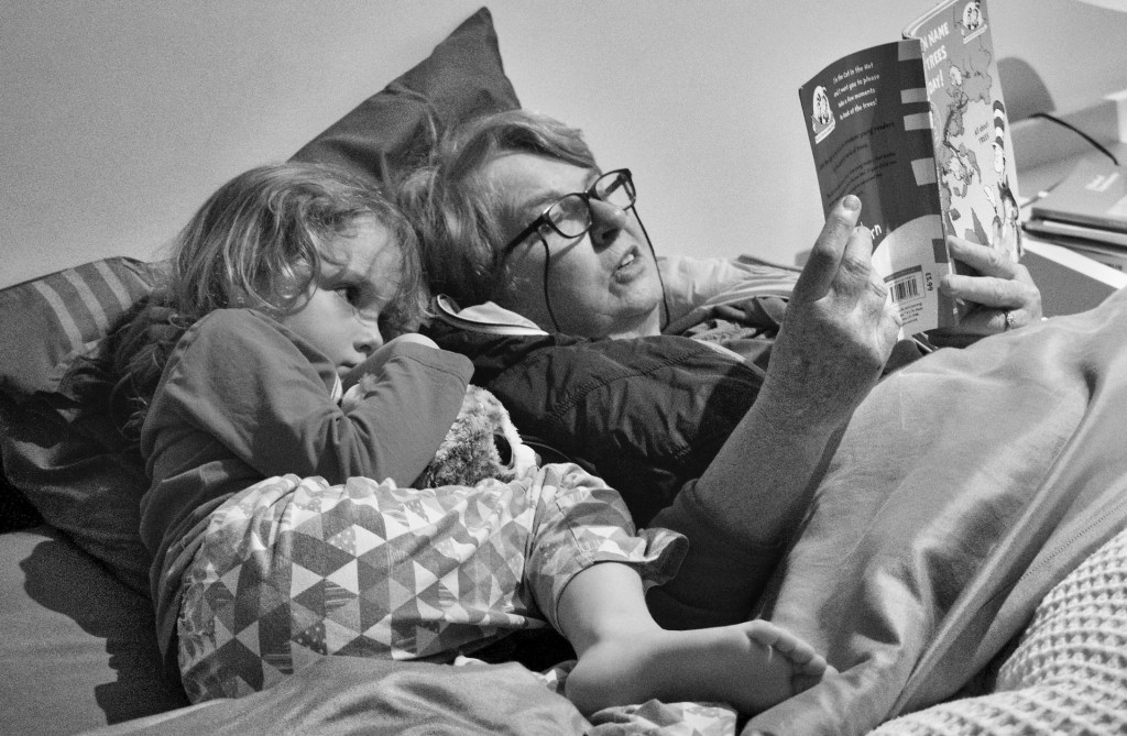 Black and white photo of the joy of reading aloud with a woman and a little girl lying in bed while the woman reads Horton Hears a Who aloud.