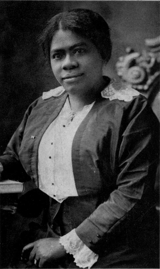 portrait photograph of middle aged Mary Mcleod Bethune sitting in a chair and looking at the camera with a confident look on her face that says she lights the way