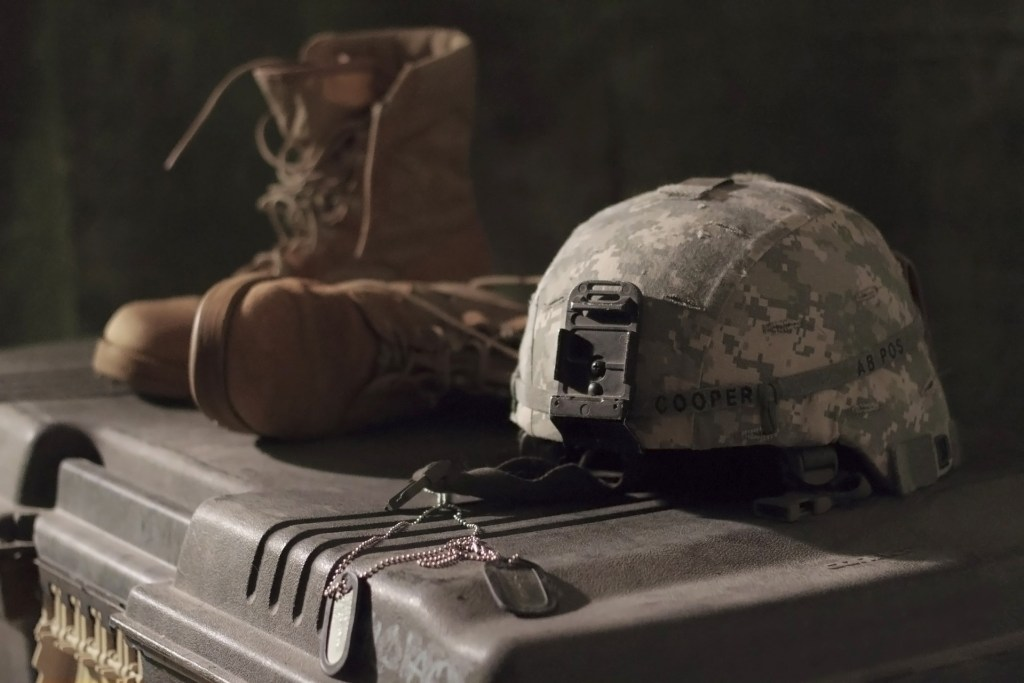 image of a pair of combat boots, a helmet, and dog tags on a metal foot locker--remember women who made the final sacrifice
