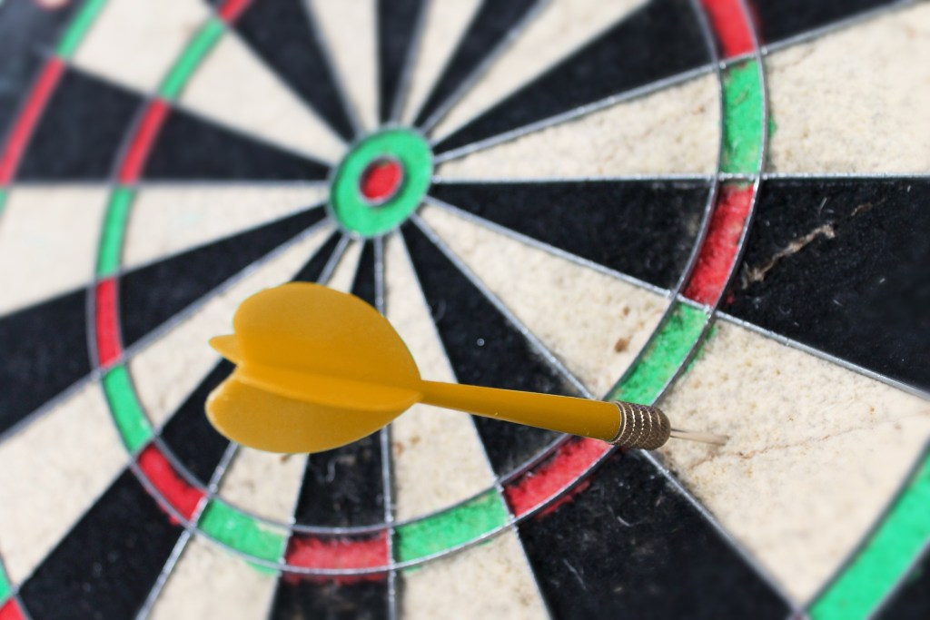 image of a dart board with a yellow dart between the first and second ring--the ups and downs of progress means close but no bullseye