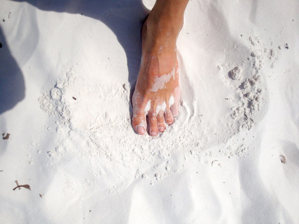 image of a woman's foot in white sand