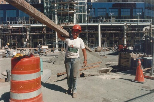 Photo of a female construction worker carrying a long beam over her shoulder.