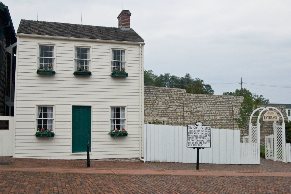 Photograph of Mark Twains boyhood home and museum with sign identifying that the white fence behind it was Tom Sawyer's fence one place for an awesome reading vacation