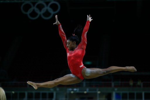 Photo of Simon Biles in a red long-sleeve leotard, mid-air during a gymnastics routine.