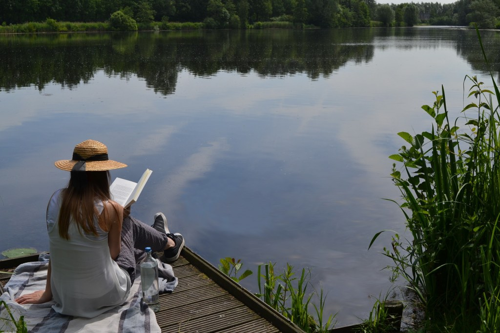Photo of a woman reading, on a dock with still water reflecting the sky and the  trees surrounding the lake, an awesome reading vacation for some.