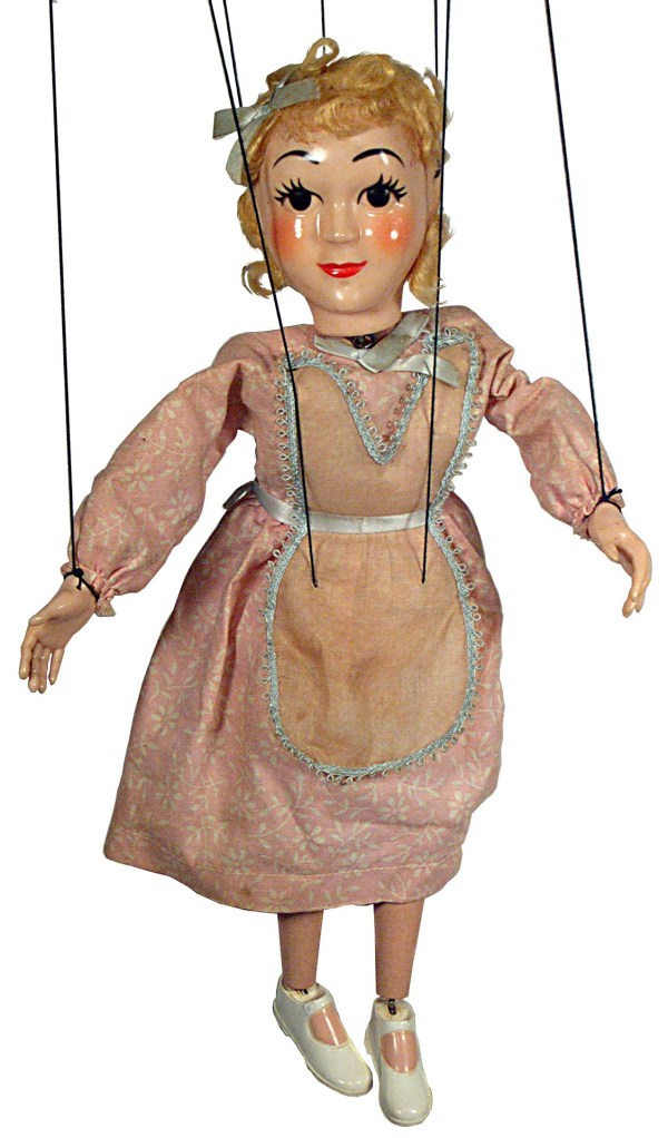 A wooden marionette with hair, a painted face and a dress but still attached to strings.
