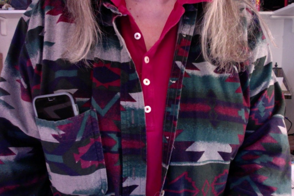 Image of woman in indian print flannel shirt with an iPhone peeking out of the chest pocket.