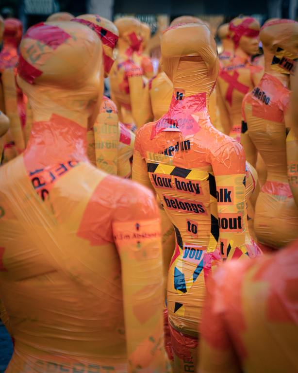 """Photo of the backs of many female manikins covered in yellow and red caution tape with the message """"your body belongs to you on the back of one manikin"""""""