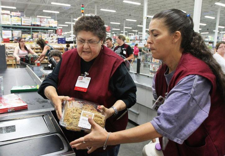 Michele Rogowskim right, of Coventry, a 12-year veteran at BJs, helps Barbara Silliman bag groceries as she trains Silliman on the register. The Providence Journal/Glenn Osmundson