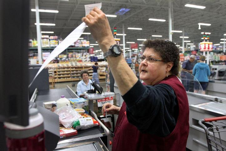 Barbara Silliman pulls a receipt from the cash register at BJ's Wholesale Club in Coventry after ringing up a customer. Silliman, who has a Ph.D. in English and teaches part-time at the University of Rhode Island, Rhode Island College and Providence College, works at BJ's to make ends meet. The Providence Journal/Glenn Osmundson